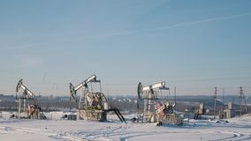 Working oil pumps in the winter field on the background of the city stock video