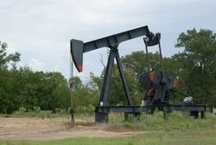 A Working Oil Well Derrick In East Texas. SONY DSC A Working Oil Well Derrick In East Texas. The well pumps oil out of the ground to a storage tank and a tanker stock images