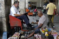 Working old shoeshiner, city Recife, Brazil. A normal Brazilian street view, shoe shiner polish the shoes of a customer who is sitting in a high chair. Unusually Stock Photo
