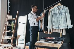 Free Working On New Order. Thoughtful Young Man Choosing Clothes From Stock Image - 110287861