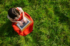 Working online in nature. A young woman sitting on the grass using a laptop computer Stock Photos