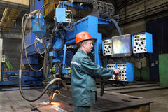 Working operator controls welding robot, standing at control pan Royalty Free Stock Images