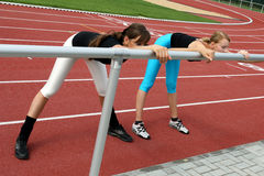 Working out. Two young girls stretching at the track Stock Photo