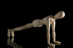 Working out. Wooden figure with a black back ground Stock Photos