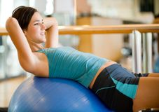 Working Out. A young woman working out in a gym Stock Image