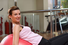 Working out on a Ball. A young woman exercising at the gym on a red pilated exercise ball Stock Images