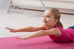 Working out is the best hobby. Keeping healthy lifestyle. Close ou of cute little girl is lying and stretching while working out at yoga mat Stock Photo