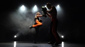 Development of straight kicks kickboxing on boxing paws. Light from behind. Smoke background. Working out of direct blows of kickboxing on boxing paws the girl stock video