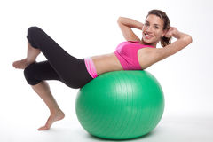Working Out Fitness Ball. Athletic woman doing crunches on a fitball Royalty Free Stock Photo