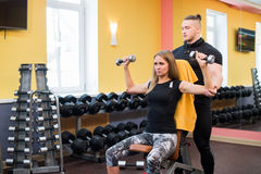 Working out in gym: Beutiful yong woman doing dumbbell excercise sitting on bench while muscular trainer watching and. Working out in gym: Beutiful yong women Royalty Free Stock Image