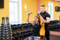 Working out in gym: Beutiful yong woman doing dumbbell excercise sitting on bench while muscular trainer watching and. Working out in gym: Beutiful yong women Stock Image