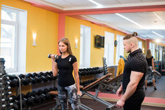 Working out in gym: Beutiful yong woman doing dumbbell excercise sitting on bench while muscular trainer watching and. Working out in gym: Beutiful yong women Royalty Free Stock Images