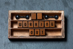 Working out gym concept heading. Aged box, wooden cubes with old style letters, black dumbbells. Gray stone textured Royalty Free Stock Photos