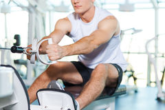 Working out in gym. Cropped image of concentrated young man working out in gym Stock Photo