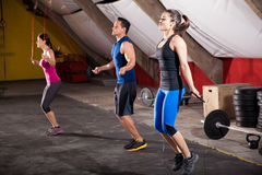 Working out with a jump rope. Group of athletic people using jump ropes for their workout in a cross-training gym Stock Photography