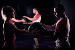 Working out in pairs, working out in the gym with personal trainer. Helping with loosing weight,training in pairs. Man and women workout wit medicine ball in gym Royalty Free Stock Photos