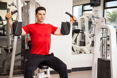 Working out on pec deck machine. Handsome young man using the pec deck machine to work on his muscles at the gym Royalty Free Stock Photos