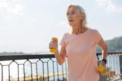 Senior lady jogging with dumbbells stock photos