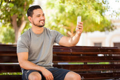 Working out and taking selfie at a park. Attractive young man with sporty outfit taking a selfie while sitting in a park bench before exercising outdoors Royalty Free Stock Image