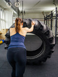 Working out with a tractor tire. Photo of a young woman training in the gym with a tractor tire Stock Photos