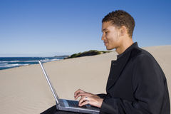 Working Outdoors. Young professional working on a laptop at the beach Stock Photo