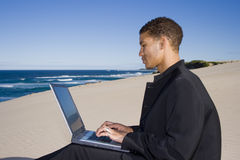 Working Outdoors. Young professional working on a laptop at the beach Royalty Free Stock Photography