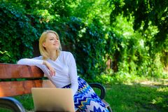Working outdoors. Casual and part time outdoor jobs. Girl sit bench with notebook. Woman with laptop works in park enjoy. Green nature and fresh air. Workplace royalty free stock photo