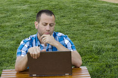 Working outdoors on a lap top computer. Man sitting and looking at his lap top at a picnic table outside in the grass wearing a plaid shirt Royalty Free Stock Image