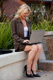 Working outside. Attractive caucasian forties businesswoman sitting outside working on laptop Royalty Free Stock Photo