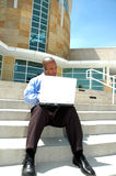 Working Outside. Man sits outside on steps of office building and works on his computer Lap top on this beautiful sunny day Royalty Free Stock Image