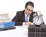 Working Overtime. A punctual businessman is working with a clock Royalty Free Stock Image