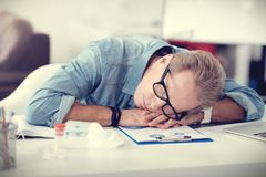 Tired nice man sleeping at his workplace Royalty Free Stock Photos