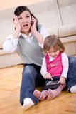 Working and parenting. Mother working at home with daughter Royalty Free Stock Image