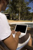 Working on a Park Bench. A young man sitting by the pool working on a laptop with screen visible Royalty Free Stock Images