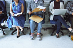 Working people. Business people sitting on chairs along the wall and working Stock Photo