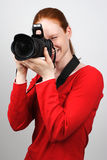 Working Photographer. A young and happy female photographer taking a photo Stock Image
