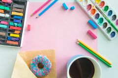 Working place of the artist with the drawing tools, a donut and coffee, and a blank sheet of paper mock up stock images