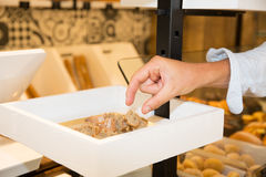 Working place at bakery, man hands picking piece of bread Royalty Free Stock Photo