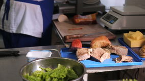 Working place of cook in an apron in kitchen, public canteen. Use for cooking recipes, for compliance need scales to accurately measure ingredients for meals stock video footage