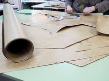 Working place in design studio. on the table a roll of cardboard and paper details. The designer is working on creating patterns, on the table is a roll of stock image