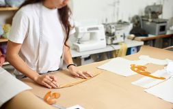 Workplace in modern design studio. Female designer creating exclusive flat paper clothing patterns. Working place in design studio. Young female designer stock photography