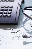 Working place office desk table headset glasses telephone Stock Image