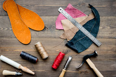 Working place of shoemaker. Skin and tools on brown wooden desk background top view Stock Images