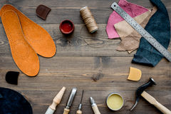 Working place of shoemaker. Skin and tools on brown wooden desk background top view copypace Royalty Free Stock Image