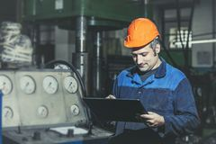 Working in the plant with tablet in hands on the background of t royalty free stock images