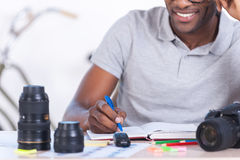 Working with pleasure. Cropped image of handsome young African man in casual wear sitting at his working place and writing something in his note pad Stock Images