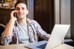 Working with pleasure. Top view of happy young man talking on the mobile phone and looking at his laptop while sitting at the desk. With bookshelf in the Royalty Free Stock Images