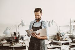 Working. Portrait of young male jeweler in apron writing in notebook royalty free stock photos