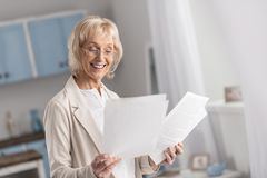 Attractive mature businesswoman collecting data. Always working. Positive joyful mature businesswoman looking down while working with documentation and wearing Stock Image