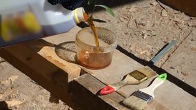 Working pouring brown liquid oil from can in the jar stock footage